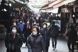 Folk med munnbind spaserer på et marked i Seoul fredag. Sør-Korea opplever nå det største smitteutbruddet siden tidlig i år. Foto: Ahn Young-joon / AP / NTB