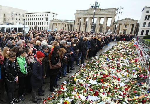 People observe a minute of silence in tribute to victims of Friday's attacks in Paris in front of French embassy close to Brandenburg Gate in Berlin