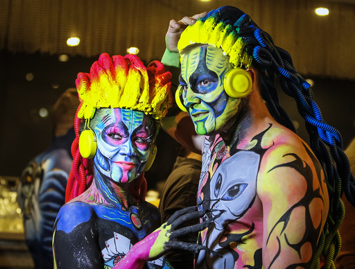 Models pose backstage during a body art festival in Almaty