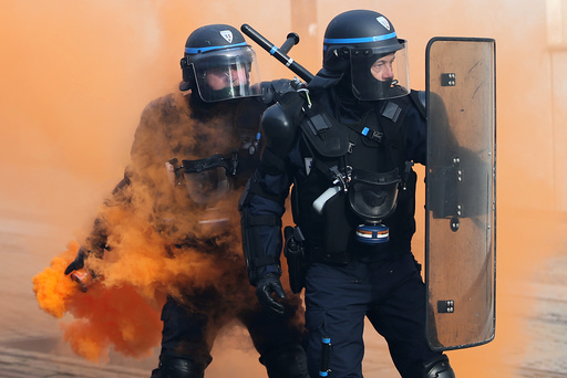 French CRS riot police face off with protestors during a demonstration against French government reforms in Nantes