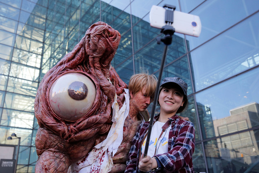 Chen Yifa from China poses for a selfie with a man dressed as William Birkin from Resident Evil at New York Comic Con in Manhattan