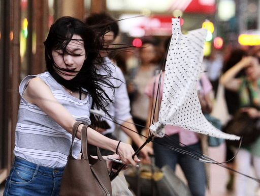 A woman holds her umbrella while walking against strong winds as Typhoon Soudelor approaches Taiwan in Taipei