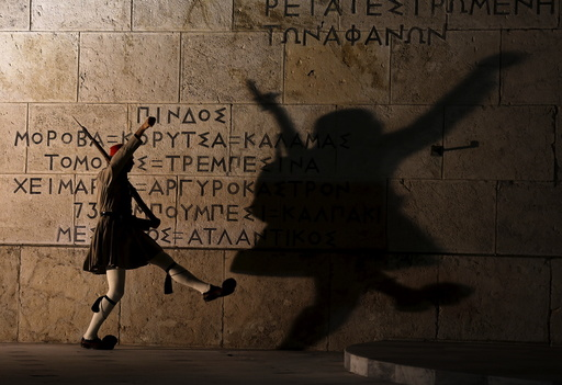 A Greek presidential guard performs a ceremonial march at the Tomb of the Unknown Soldier in front of the parliament building in Athens