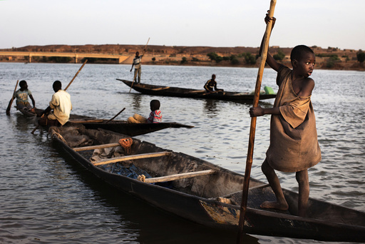 Men and boys fish in canoes in the Niger River in Gao