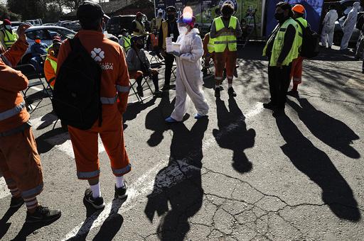 En helsearbeider deler ut prøvesvar på koronatester til en gruppe arbeidere på et testsenter i Chiles hovedstad Santiago i juli. Foto: Esteban Felix / AP / NTB scanpix