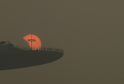 People watch the sun set from the observatory deck of the Marina Bay Sands hotel in Singapore