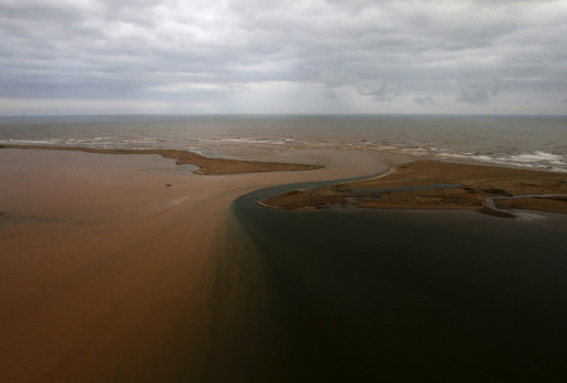An aerial view of the mouth of Rio Doce (Doce River), which was flooded with mud after a dam owned by Vale SA and BHP Billiton Ltd burst, is seen as the river joins the sea on the coast of Espirito Santo, in Regencia Village, Brazil