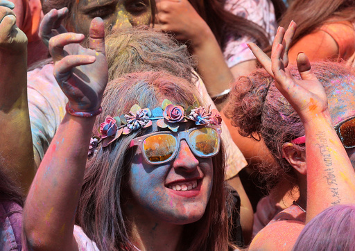 Woman coloured by powder dances during the Holi festival in Santa Coloma de Gramenet