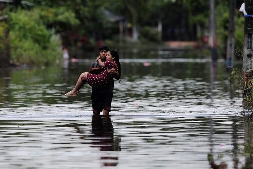 A man carries his wife on a flooded street after heavy rainfall in Milagro