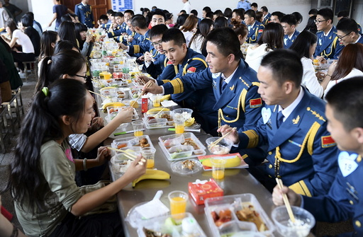 Soldiers of People's Liberation Army of China Air Force talk to women as they have lunch together during a match-making event for military personnel, at a military base in Wuhan