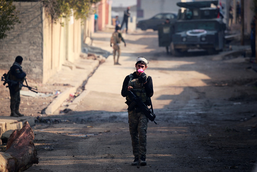 A member of Iraqi rapid response forces holds flower during battle with Islamic State militants in the Mithaq district