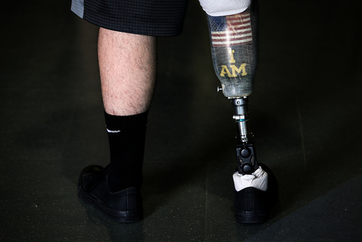 Wounded warrior Steven Davis poses for a photo with his prosthetic leg with a U.S. flag and Invictus Games I Am slogan on it at the Invictus Games in Orlando Florida