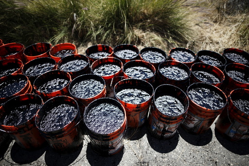 Buckets of oil volunteers carried from an oil slick along the coast of Refugio State Beach are seen in Goleta