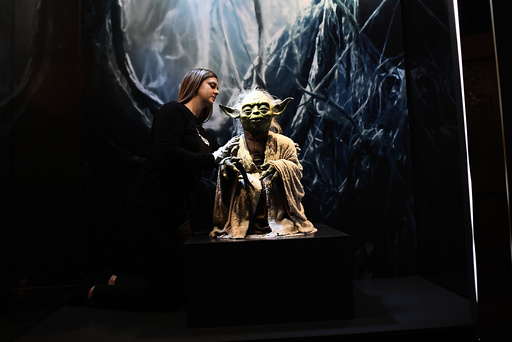 Kathy Smeaton, helps unpack the Yoda puppet used in the original movies, at the Star Wars Identities exhibition at the 02 in London