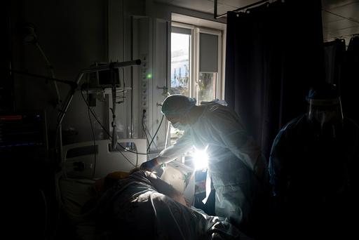 En lege på intensivavdelingen på sykehuset i Rivne snakker med en pasient med covid-19. Foto: Evgenij Maloletka / AP / NTB