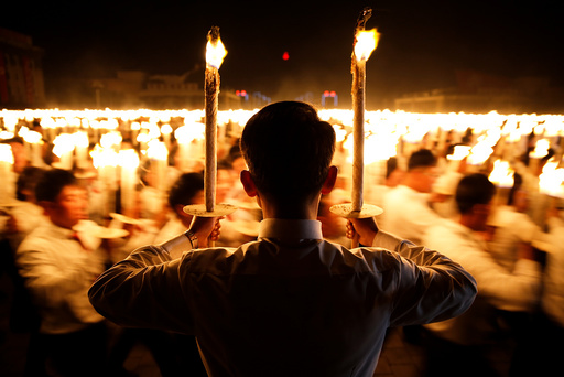Participants carry torches during a torchlight procession in the capital's main ceremonial square, a day after the ruling Workers' Party of Korea party wrapped up its first congress in 36 years, in Pyongyang