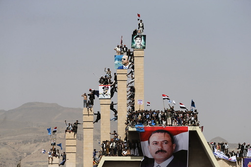 Supporters of Yemen's former President Ali Abdullah Saleh climb pillars of the Unknown Soldier Monument during a rally marking one year of Saudi-led air strikes in Yemen's capital Sanaa
