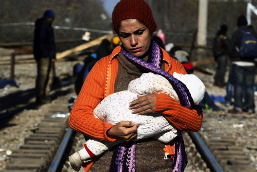 A stranded migrant holds a baby as she waits next to the Greek-Macedonian border near to the Greek village of Idomeni