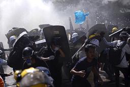 Demonstranter forsøker å komme seg unna opprørspoliti som avfyrer tåregass i Yangon mandag. Foto: AP / NTB