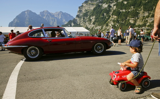 A boy looks at a vintage Jaguar E-Type sports car driving past during the British Car Meeting 2015 in the village of Mollis