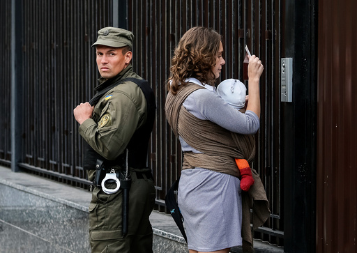A woman shows her passport to enter the Russian embassy and take part in the Russian parliamentary election as member of the National Guard stands guard in Kiev