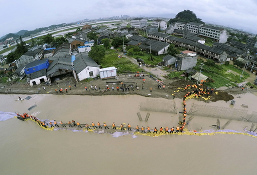 An aerial view shows PLA soldiers and local residents placing sand bags to block the flood water after a dam breached under the influence of Typhoon Soudelor, in Pingyang county