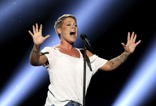 "FILE - In this Jan. 28, 2018, file photo, Pink performs ""Wild Hearts Can't Be Broken"" at the 60th annual Grammy Awards at Madison Square Garden in New York. Pink says she had COVID-19 and is donating $500,000 each to two emergency funds. In a pair of tweets posted Friday, April 3, 2020, the singer says she tested positive after she and her three-year-old son started displaying symptoms two weeks ago. (Photo by Matt Sayles/Invision/AP, File)"