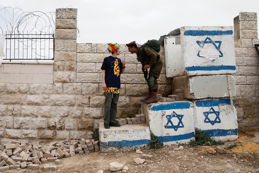 A man dressed in costume chats with an Israeli soldier as he takes part in a parade marking the Jewish holiday of Purim in the West Bank city of Hebron