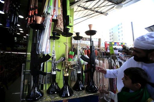 People inspect hookahs shaped like rifles on display for sale in a souk at the port city of Sidon