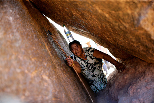 Catholic pilgrim Matilde Madalena de Jesus crawls on a rocky trail carrying a bottle of water on her head during the annual pilgrimage of the dead in the city of Juazeiro do Norte