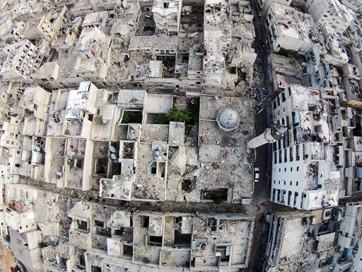 A aerial view shows a damaged mosque and surrounding buildings in the Al-Maysar neighbourhood of Aleppo