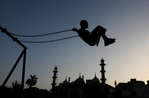 A boy is silhouetted as he plays on a swing during sunset hours near a mosque in Karachi,