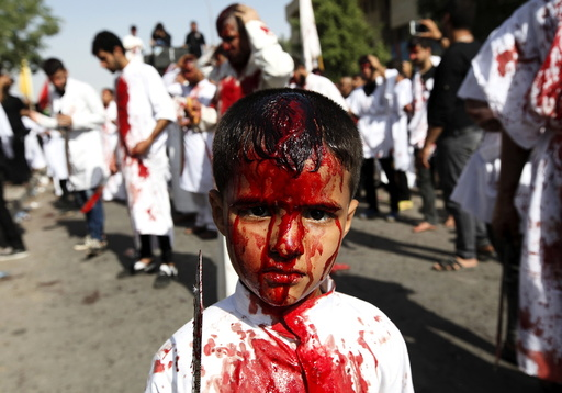 An Iraqi Shi'ite boy poses for a photograph as Iraq Shi'ite Muslims commemorate Ashura in Baghdad