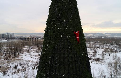 A climber dressed as Santa Claus decorates a Christmas tree in Krasnoyarsk