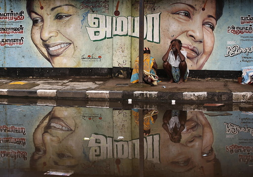 A flood-affected couple sits along a flooded roadside under a picture of Jayalalithaa, CM of Tamil Nadu, in Chennai