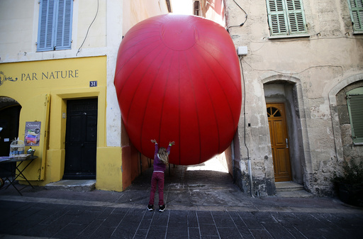 A child plays with a huge red ball which is installed between two buildings as part of the RedBall Project by artist Kurt Perschke in Marseille