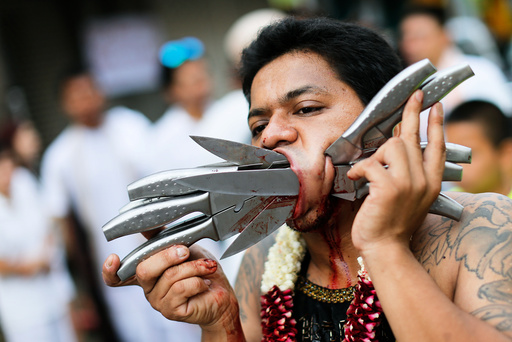 A devotee of the Chinese Ban Tha Rue shrine with knives piercing his face takes part in a procession celebrating the annual vegetarian festival in Phuket