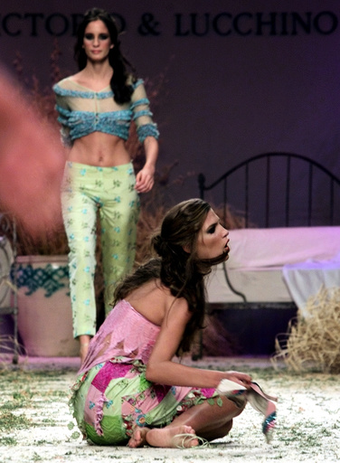 A MODEL FALLS TO THE FLOOR DURING VITORIO & LUCCINO'S FASHION SHOW.
