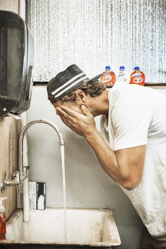 Carpenter washing face in workshop