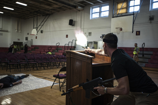 Scott of security contractor Camber Corp impersonates a hostile shooter during a training exercise at Quantico Middle High School in Quantico