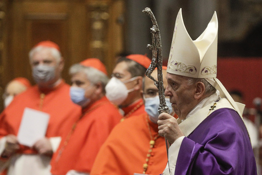 FILE - In this file photo dated  Sunday, Nov. 29, 2020, Pope Francis holds his pastoral staff as he arrives to celebrate Mass, at St. Peter's Basilica.  Pope Francis has changed church law to explicitly allow women to do more things during Mass, Monday Jan. 11, 2021, while reaffirming they cannot be priests. (AP Photo/Gregorio Borgia, FILE)