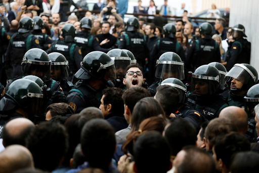 Scuffles break out as Spanish Civil Guard officers force their way through a crowd and into a polling station for the banned independence referendum in Sant Julia de Ramis