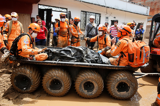 Rescue members recover a body in a house after flooding and mudslides caused by heavy rains leading several rivers to overflow, pushing sediment and rocks into buildings and roads, in Mocoa