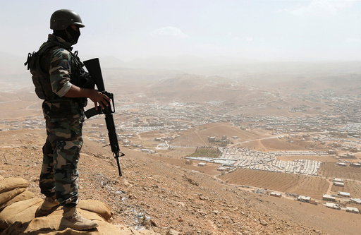 A Lebanese soldier carries his weapon as he stands on sandbags at an army post in the hills above the Lebanese town of Arsal, near the border with Syria