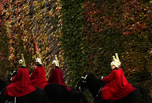 Members of the Household Cavalry ride past autumn foliage in central London, Britain