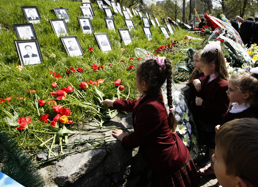 Children lay flowers at a monument to victims of the Chernobyl nuclear disaster in Kiev