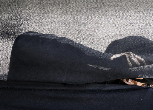 Woman looks through a tent during a gathering by Houthi loyalists against Saudi-led air strikes in Yemen's capital Sanaa
