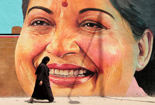 A woman walks past a portrait of J. Jayalalithaa, Chief Minister of the southern state of Tamil Nadu, in Chennai