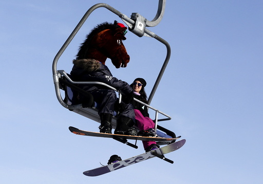 A snowboarder wearing a mask of a horse head rides a lift uphill at the Bobrovy Log ski resort in the suburbs of Krasnoyarsk