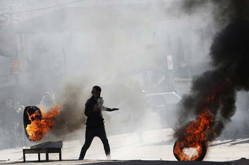 Palestinian protester runs between burning tyres during clashes with Israeli troops in the West Bank city of Hebron